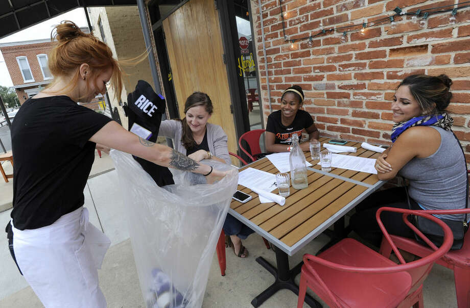 Bartender Abby Hopper, left, of Baltimore, collects a Ray Rice Baltimore Ravens football jersey from Sam DeMarco, second from left, of Baltimore, who dined with Allie Hurtt, third from left, of Baltimore, and Darya Safai, right, of Baltimore at Hersh's Pizza and Drinks, a Baltimore restaurant that offered a free personal pizza in exchange for Rice jerseys Monday, Sept. 8, 2014. Rice was let go by the Ravens on Monday and suspended indefinitely by the NFL after a video was released showing the running back striking his then-fiancee in February. (AP Photo/Steve Ruark)