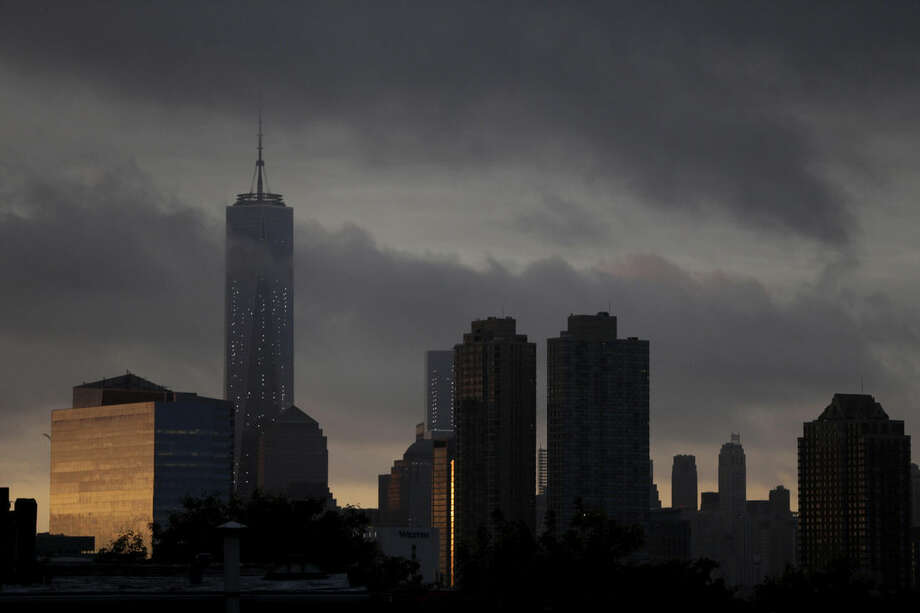 Storm clouds roll over 1 World Trade Center, left, seen from The Heights neighborhood of Jersey City, N.J., at sunrise, Thursday, Sept. 11, 2014. Thirteen years after 9/11 forever changed the New York skyline, officials say developments at the World Trade Center are on track and on budget. (AP Photo/Julio Cortez)
