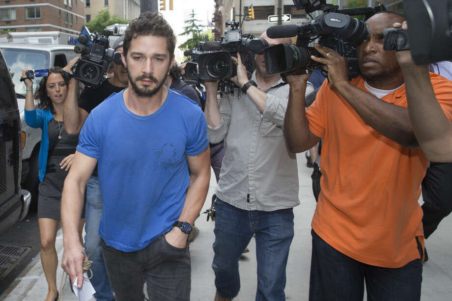 "FILE - In this June 27, 2014 file photo, actor Shia LaBeouf walks through the media after leaving Midtown Community Court in New York following his arrest the previous day for yelling obscenities at the Broadway show ""Cabaret."" LaBeouf on Wednesday, Sept. 10, 2014 pleaded guilty to disorderly conduct stemming from the incident. (AP Photo/John Minchillo, File)"