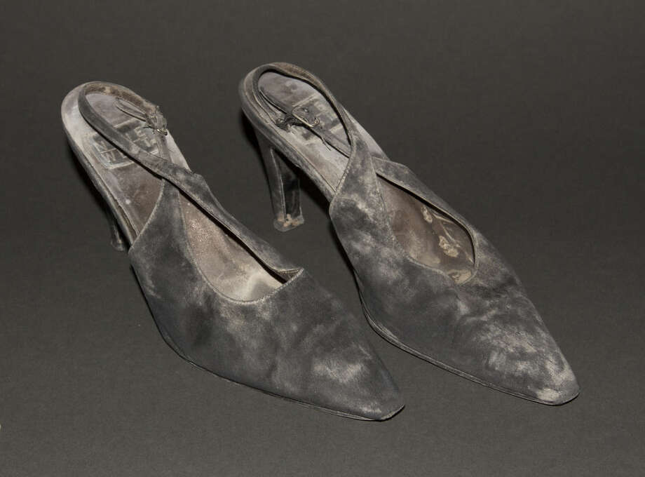 """This July 29, 2014 file photo provided by the National September 11 Memorial and Museum, shows a pair of high-heel shoes worn by JoAnne """"JoJo"""" Capestro while descending 87 floors of stairs to escape a World Trade center tower on Sept. 11, 2001. The shoes are among the clothes, wallets, helmets, and other personal effects donated to the museum by survivors and those who worked at the site in the attacks' aftermath. (AP Photo/National September Memorial and Museum, John D Childs)"""