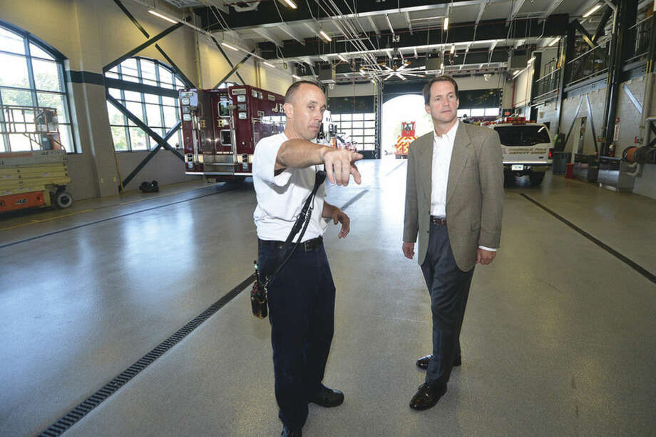 Hour Photo/Alex von Kleydorff Norwalk Fire Capt. Adam Markowitz shows Congressman Himes the training wall off the Apparatus Bay at Fire Headquarters