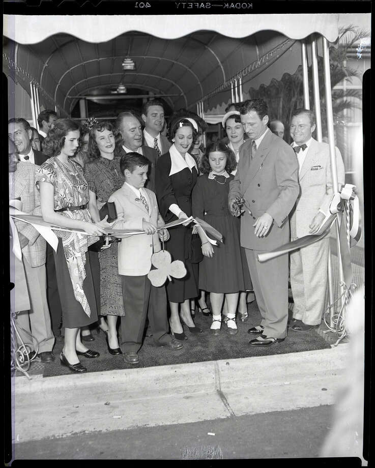 03/17/1949 - Ribbon cutting ceremonies at the grand opening of the Shamrock Hotel. two of Glenn McCarthy's daughters (not sure of order), Mary Margaret McCarthy and Glenna Lee McCarthy are on the left; young Glenn McCarthy Jr.; behind him are entertainer Pat O'Brien and actor Robert Paige; actress Dorothy Lamour; Glenn McCarthy's youngest daughter, Faustine McCarthy; Mrs. Glenn (Faustine) McCarthy; Glenn H. McCarthy holding the scissors. Photo: HP Staff / Houston Post files