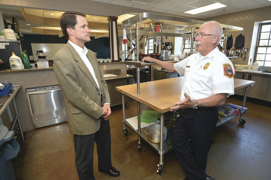 Hour Photo/Alex von Kleydorff Norwalk Fire Chief Denis McCarthy shows Congressman Jim Himes the kitchen and dinning area, one of the areas he says is used everyday in the new fire headquaters.
