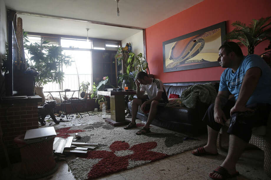 Israelis sit in their home that was hit by a rocket fired from the northern Gaza Strip Tuesday morning, in the costal city of Ashkelon, Israel, Tuesday, Aug. 26, 2014. (AP Photo/Tsafrir Abayov)