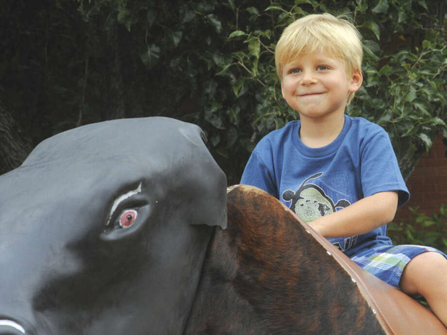Grayson Lapine 5, rides a mechanical bull Sunday at the Blues Views and BBQ Festival in Westport. Hour photo/Matthew Vinci