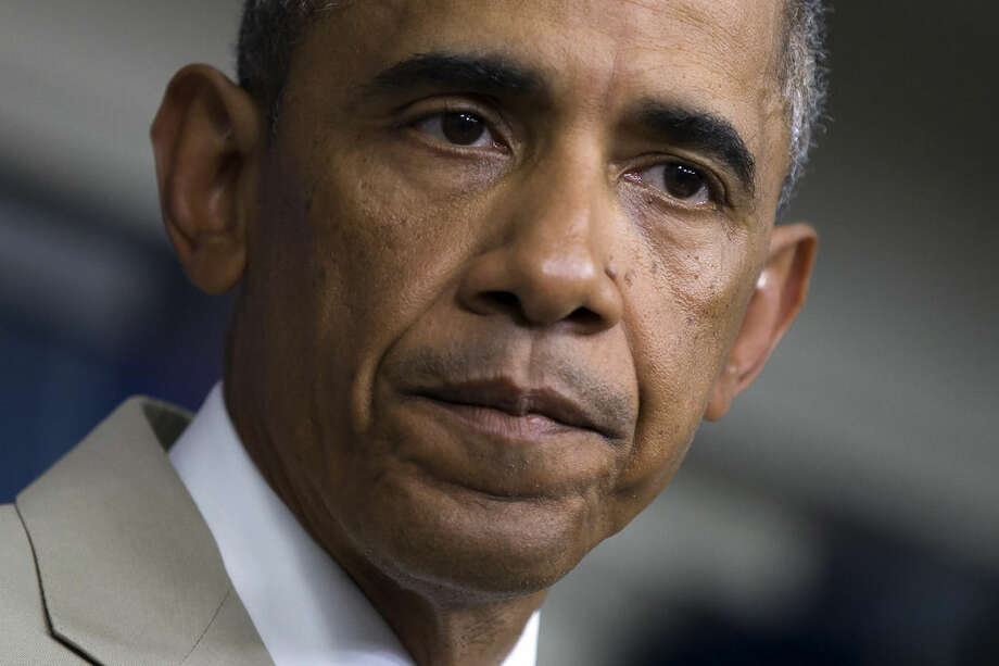 President Barack Obama listens in the James Brady Press Briefing Room of the White House in Washington, Thursday, Aug. 28, 2014, where he spoke about the economy, Iraq, and Ukraine, before convening a meeting with his national security team on the militant threat in Syria and Iraq. (AP Photo/Evan Vucci)