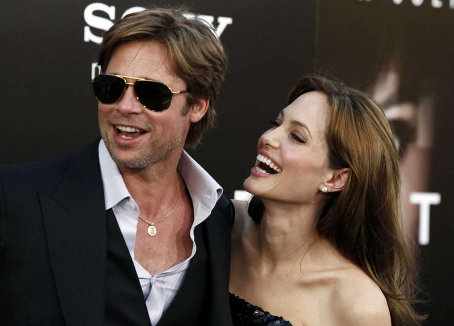 """FILE - In this Monday, July 19, 2010, file photo, cast member Angelina Jolie, right and Brad Pitt arrive at the premiere of """"Salt"""" in Los Angeles. Jolie and Pitt were married Saturday, Aug. 23, 2014, in France, according to a spokesman for the couple. (AP Photo/Matt Sayles, File)"""