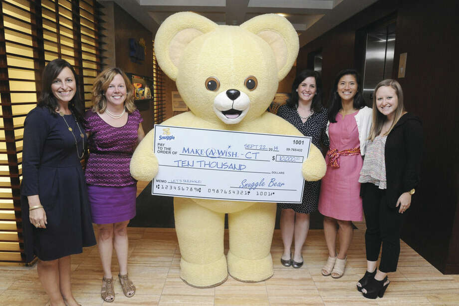 Wilton-based Sun Products Corporation hostied a company-wide celebration for Snuggle Bear's 30th birthday at its headquarters. To mark the occasion and contribute to the local community, Snuggle Bear and the company will be donating an oversize $10,000 check to Make-A-Wish Foundation of Connecticut. From left, Tara Navara and Pam Keough with Make a Wish, Sun Corporation emplotyees, Sara Mayer, Associate Brand Manager and Bi Bie Wu and Jessica Davidson. Photo/Matthew Vinci