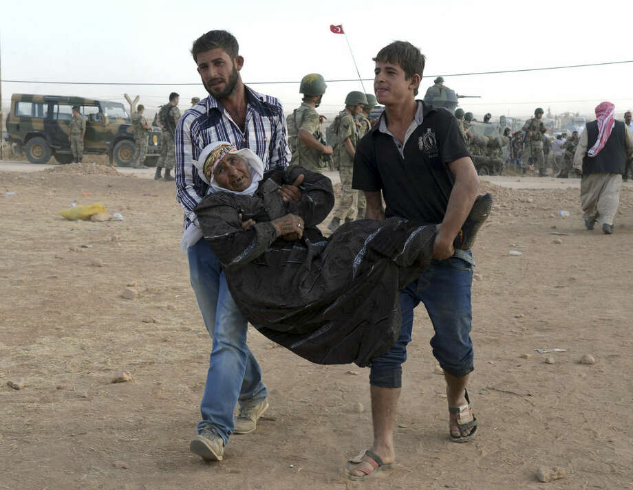 Syrian refugees carry a sick person at the border in Suruc, Turkey, late Saturday, Sept. 20, 2014. Several thousand Syrians, most of them Kurds, crossed into Turkey on Friday to find refuge from Islamic State militants who have barreled through dozens of Kurdish villages in northern Syria in the past 48 hours.(AP Photo)