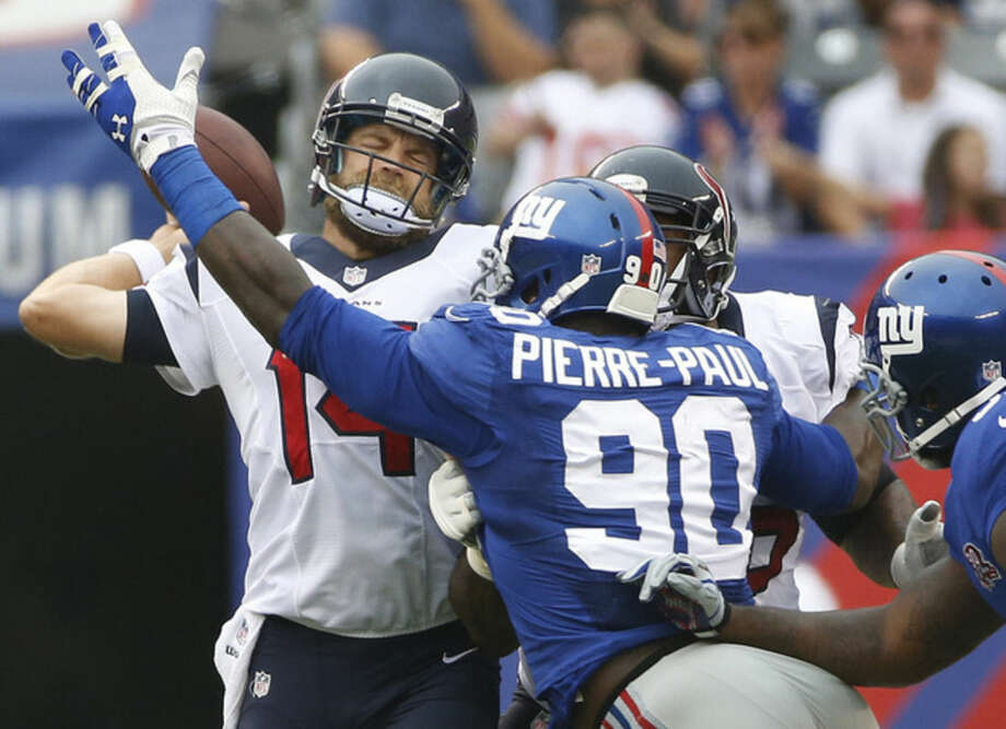 Houston Texans quarterback Ryan Fitzpatrick (14) throws under pressure from New York Giants defensive end Jason Pierre-Paul (90) in the first quarter of an NFL football game, Sunday, Sept. 21, 2014, in East Rutherford, N.J. Fitzpatrick threw an interception on the play. (AP Photo/Kathy Willens)