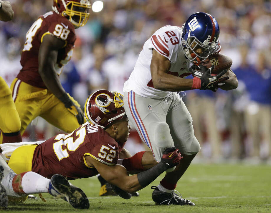 Washington Redskins inside linebacker Keenan Robinson (52) loses his helmet as he tries to stop New York Giants running back Rashad Jennings (23) during the first half of an NFL football game in Landover, Md., Thursday, Sept. 25, 2014. (AP Photo/Patrick Semansky)