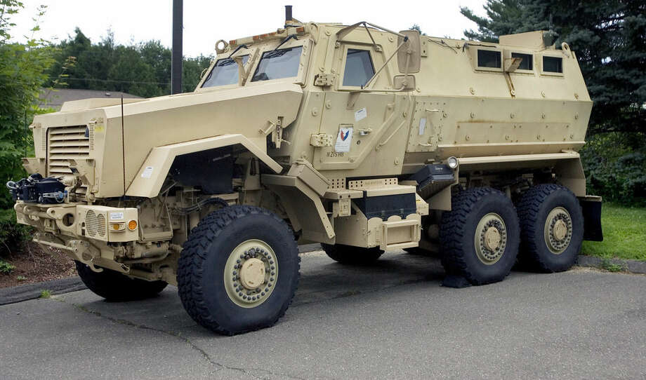 FILE- In this July 16, 2014 file photo, a Mine-Resistant Ambush Protected vehicle sits in front of police headquarters in Watertown, Conn. The L.A. Unified's School District police department received a MRAP vehicle like this one through a federal program. School police departments across the country have taken advantage of free military surplus gear, stocking up on mine resistant vehicles, grenade launchers and scores of M16 rifles. At least 26 school districts across the country participate in the Pentagon's surplus program, which has come under scrutiny after a militarized police response to protests in Ferguson, Missouri. (AP Photo/The Republican-American, Steven Valenti, File)