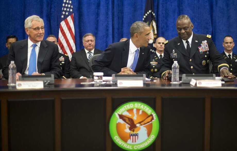 President Barack Obama, center, with Sec. of Defense Chuck Hagel, left, and Gen. Lloyd J. Austin III, right, Commander of the US Central Command (CentCom), before the start of a briefing at MacDill Air Force Base, Fla., Wednesday, Sept. 17, 2014. Obama was being updated on the ongoing military campaigns in Iraq and Syria. (AP Photo/Pablo Martinez Monsivais)