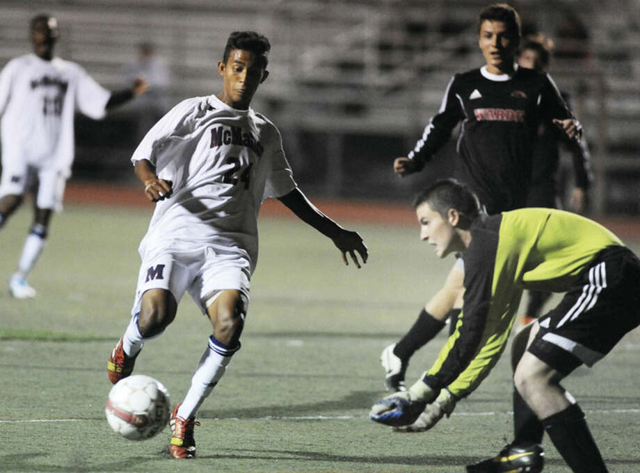 Hour photo/Matthew VinciBrien McMahon's Edison Pena, left, closes in on goal, while Fairfield Warde's Michael Lerman leans over to collect the ball during Tuesday night's game in Norwalk. McMahon won 2-1.