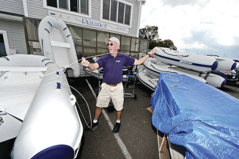 Hour photo / Erik Trautmann Rex Marine's Mike Maver sets up his Mercury display Tuesday as the Progressive Insurance Norwalk Boat Show readies to open Thursday.