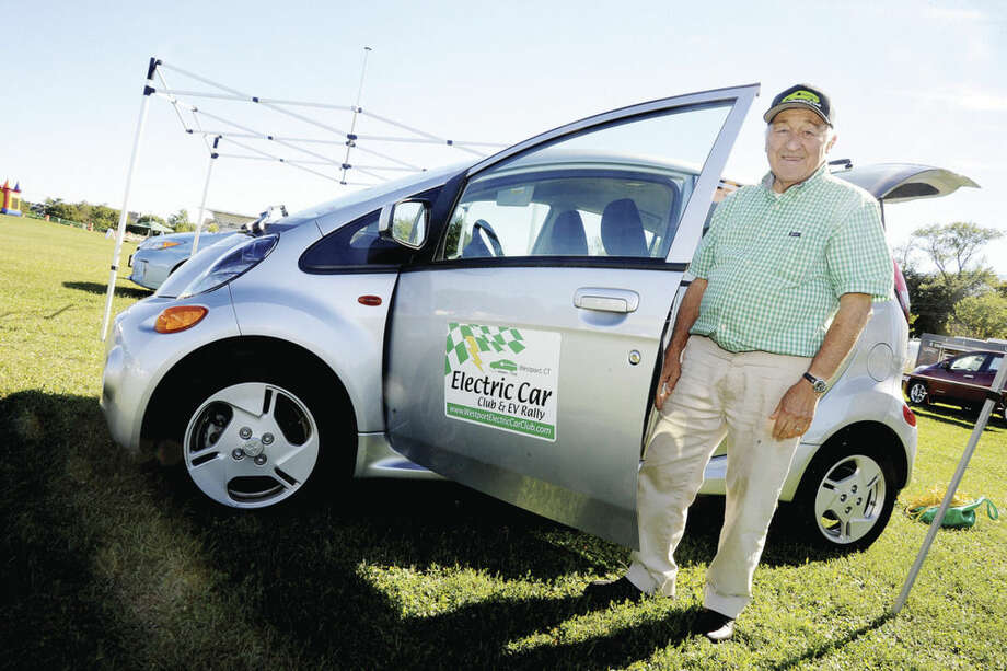 Hour photo/Matthew VinciLeo Cirino, president of the Westport Electric Car Club, poses with a car Sunday at the Live Green Connecticut! event held at Norwalk's Taylor Farm.