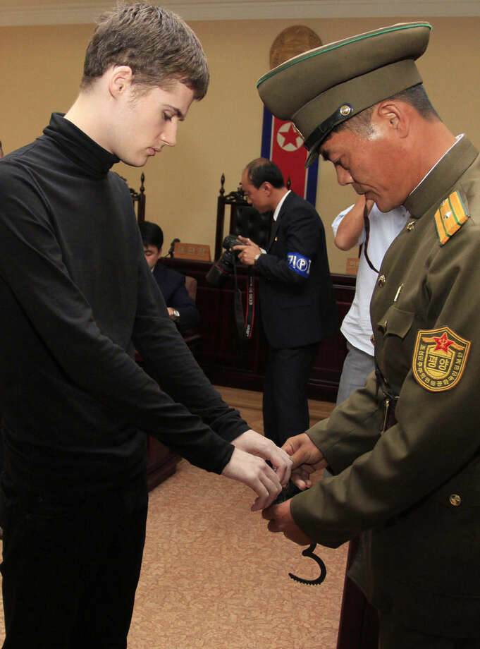 Matthew Miller, a U.S. citizen, is handcuffed after his trial at the Supreme Court in Pyongyang, North Korea, Sunday, Sept. 14, 2014. North Korea's Supreme Court on Sunday sentenced Miller to six years of hard labor for entering the country illegally and trying to commit espionage. (AP Photo/Kim Kwang Hyon)