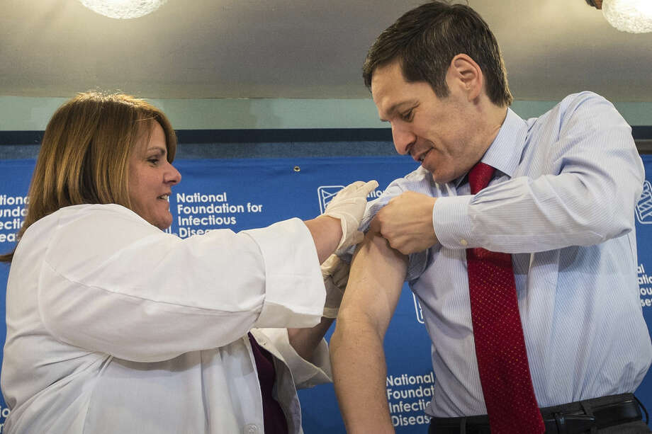 "Dr. Thomas Frieden, Director of the Centers for Disease Control and Prevention, receives a flu shot from Sharon Bonadies at the conclusion of a press conference at the National Press Club in Washington, Thursday, Sept. 18, 2014. ""Vaccination is the single most important step everyone 6 months of age and older can take to protect themselves and their families against influenza,"" said Frieden. Influenza hospitalized a surprisingly high number of young and middle-aged adults last winter, and this time around the government wants more of them vaccinated. (AP Photo/J. David Ake)"