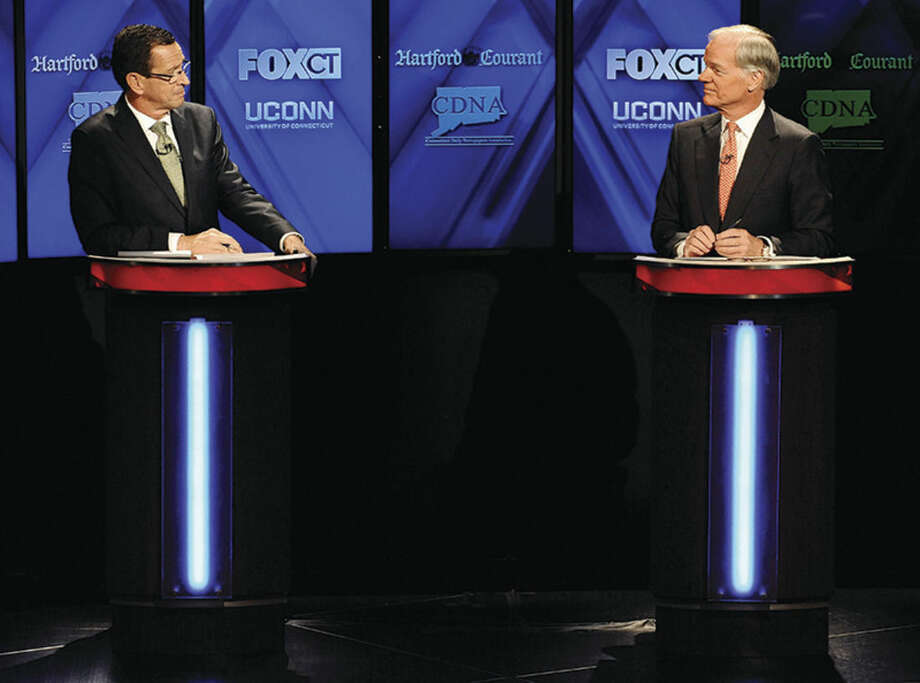 AP photo/Jessica HillIncumbent Democrat Gov. Dannel P. Malloy, left, and Republican candidate for governor Tom Foley, debate at the University of Connecticut, Thursday in Storrs.