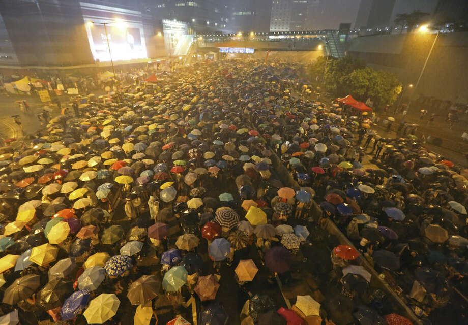 Pro-democracy protesters hold umbrellas under heavy rain in a main street near the government headquarters in Hong Kong late Tuesday, Sept. 30, 2014. The protesters demanded that Hong Kong's top leader meet with them on Tuesday and threatened wider actions if he did not, after he said China would not budge in its decision to limit voting reforms in the Asian financial hub. (AP Photo)