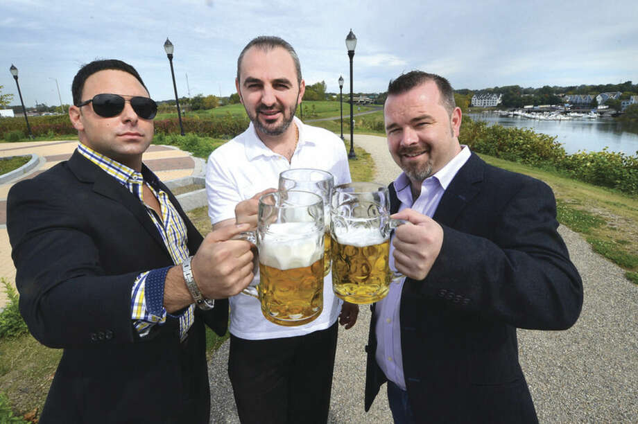 Jason Petrini, owner of Studio Marketing; Eddy Ahmetak and Niall O'Neill, co-owners of The Beer Garden SoNo, toast to the Oktoberfest set for this coming weekend at Oyster Shell Park.Hour photo/Alex von Kleydorff