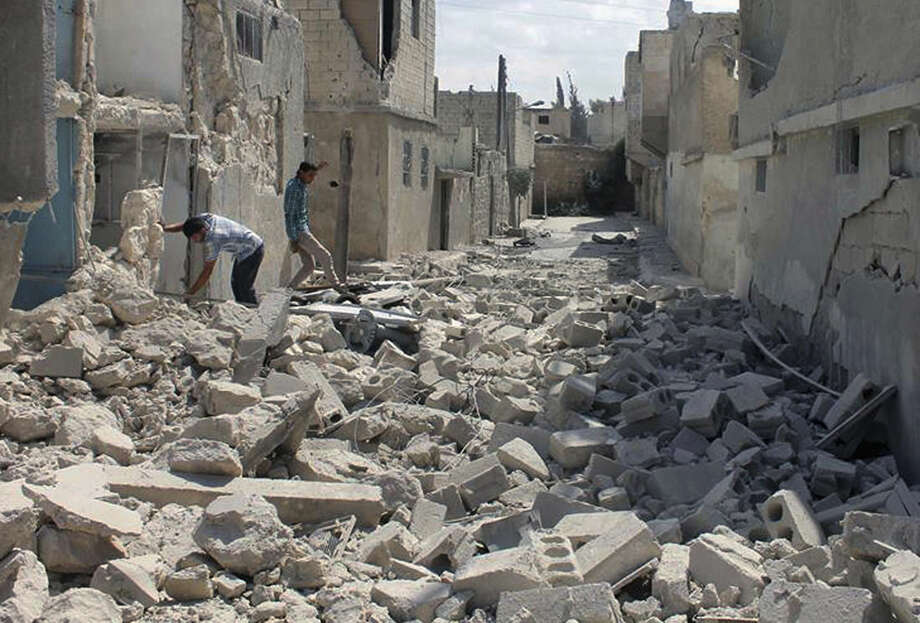 In this Saturday, Sept. 27 2014 photo, provided by the anti-government activist group Syrian Observatory for Human Rights, which has been authenticated based on its contents and other AP reporting, shows Syrians inspecting the rubble of damaged houses following a Syrian government airstrike in Aleppo, Syria. (AP Photo/Syrian Observatory for Human Rights)