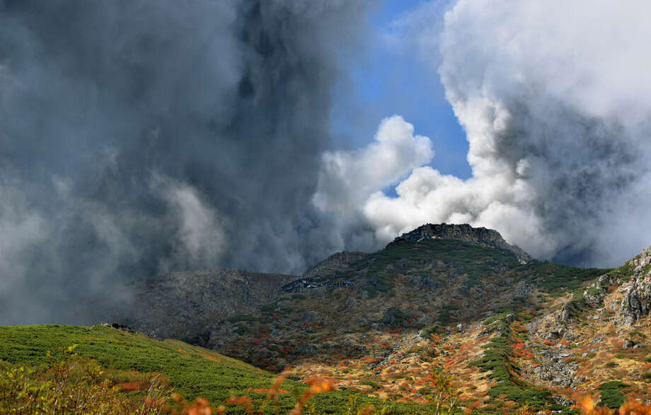 In this photo taken by an anonymous climber and was offered to Kyodo News, dense plumes rising from the summit crater of Mount Ontake cover the slope carpeted by colored autumn leaves after the volcanic mountain erupted in central Japan, Saturday, Sept. 27, 2014. With a sound likened to thunder, the 3,067-meter (10,062-foot) mountain spewed large white plumes high into the sky, sending people fleeing, covering surrounding areas in ash, injuring many climbers who were stranded in mountain lodges and areas that rescue workers have been unable to reach. (AP Photo/Kyodo News) JAPAN OUT, MANDATORY CREDIT