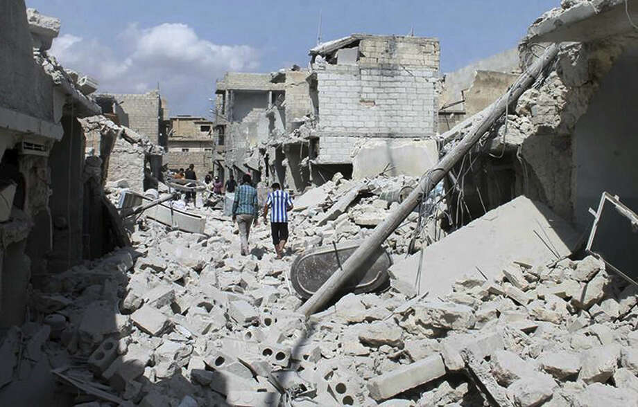 In this Saturday, Sept. 27 2014 photo, provided by the anti-government activist group Syrian Observatory for Human Rights, which has been authenticated based on its contents and other AP reporting, shows Syrians walking amid the rubble of damaged houses following a Syrian government airstrike in Aleppo, Syria. (AP Photo/Syrian Observatory for Human Rights)