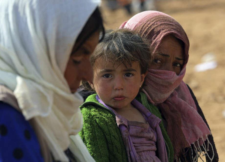 Syrian refugees, mostly Kurds from Kobani, rest after arriving at the Turkey-Syria border near Suruc, Turkey, Saturday, Sept. 27, 2014. (AP Photo/Burhan Ozbilici)