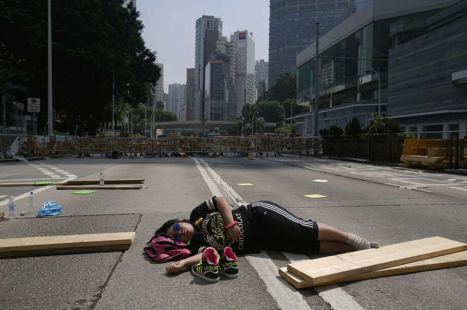 A lone pro-democracy student protester sleeps in the middle of an occupied road in Hong Kong, Saturday, Oct. 4, 2014. Bolstered by a massive rally overnight, Hong Kong's pro-democracy activists were defiant on the eighth day of protests Sunday in the face of attacks by opponents and government warnings to clear the business district streets they have occupied to press their demand for reforms. (AP Photo/Wally Santana)