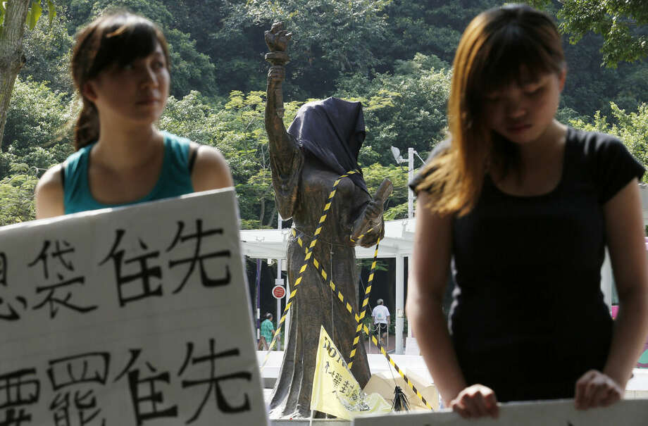 Pro-democracy student protesters hold placard, urging students to boycott classes in front of the Goddess of Democracy statue with which head covered by a black cloth to represent democracy is dead at the Chinese University of Hong Kong campus in Hong Kong, Monday, Oct. 6, 2014. Passionate student-led protests for democratic reforms in Hong Kong subsided Monday but a few hundred demonstrators remained camped out, vowing to keep up the pressure on the government until officials show they are sincere in responding to their demands. (AP Photo/Kin Cheung)