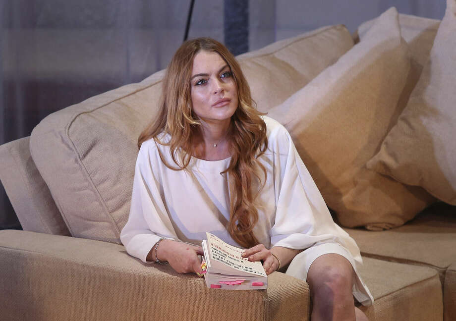 FILE - In this Tuesday, Sept. 30, 2014 file photo, U.S actress Lindsay Lohan performs a scene from the play, Speed the Plow, during a photocall at the Playhouse Theatre in central London. It wasn't a car crash, but there weren't fireworks, either. Critics have given a lukewarm welcome to Lindsay Lohan's professional stage debut, which followed months of hype and speculation about whether the wayward star was up to the job. (Photo by Joel Ryan/Invision/AP, File)
