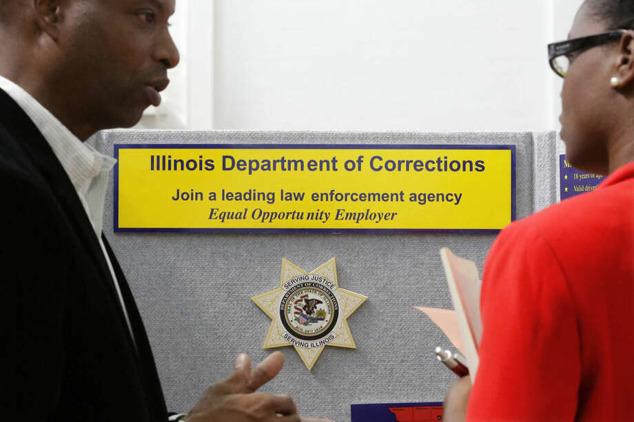 In this Sept. 25, 2014 photo, Illinois Department of Corrections employment recruiter, Forrest Ashby, left, speaks to students attending The Foot in the Door Career Fair at the University of Illinois in Springfield, Ill. The Labor Department releases employment data for September on Friday, Oct. 3, 2014. AP Photo/Seth Perlman)