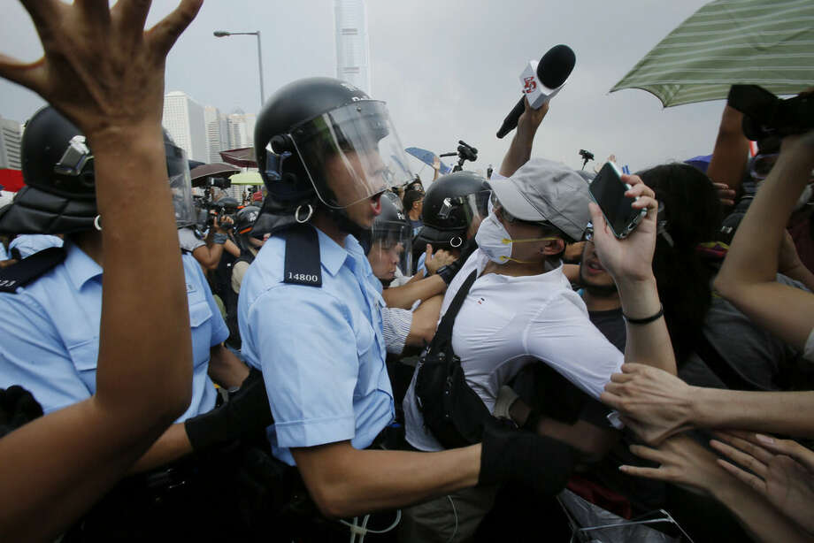 Riot police try to hold back scuffling pro-democracy protesters as an ambulance tries to leave the compound of the chief executive office in Hong Kong, Friday, Oct. 3, 2014. Hong Kong protesters on Friday welcomed an overnight offer by the territory's leader of talks to defuse the crisis over demonstrations seeking democratic reforms, though they continued to demand he resign and maintained barricades around government headquarters, frustrating staff going to work. (AP Photo/Wally Santana)