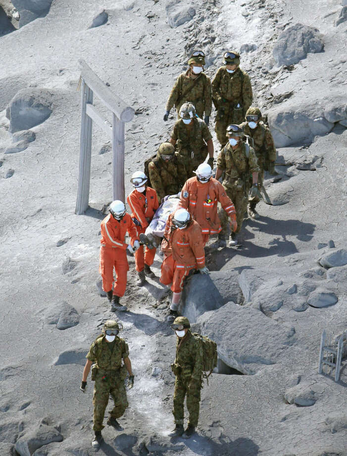 Firefighters and members of the Japan Self-Defense Forces carry a person rescued from a cabin on Mount Ontake in central Japan, Sunday, Sept. 28, 2014. Mount Ontake erupted shortly before noon Saturday, spewing large white plumes of gas and ash high into the sky and blanketing the surrounding area in ash. Rescue workers on Sunday found more than 30 people unconscious and believed to be dead near the peak of an erupting volcano, a Japanese police official said. (AP Photo/Kyodo News) JAPAN OUT, MANDATORY CREDIT