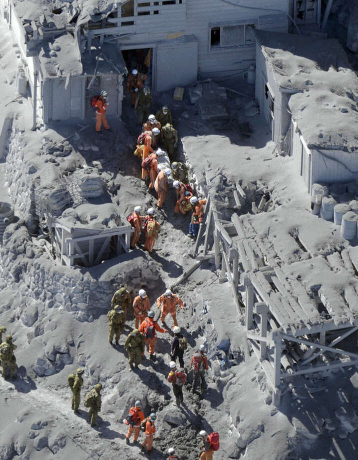 Firefighters and members of Japan's Self-Defense Forces conduct a rescue operation on Mount Ontake in central Japan, Sunday, Sept. 28, 2014. Mount Ontake erupted shortly before noon Saturday, spewing large white plumes of gas and ash high into the sky and blanketing the surrounding area in ash. An estimated 40 people were stranded at mountain lodges overnight, many injured and unable or unwilling to risk descending 3,067-meter (10,062-foot) Mount Ontake on their own. (AP Photo/Kyodo News) JAPAN OUT, MANDATORY CREDIT