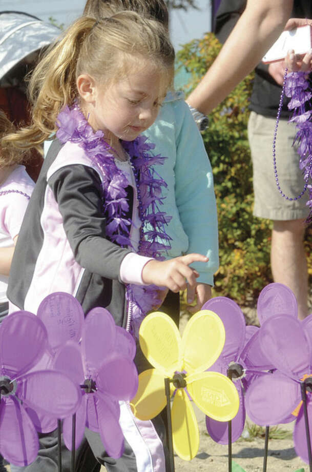 Hour photo/Matthew VinciSofia Yann 4, plants a flower in the Garden of Hope at Calf Pasture Beach Sunday at the Fairfield County Walk to End Altzheimer's.