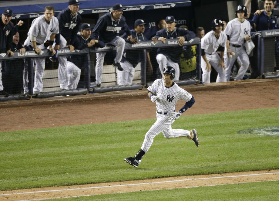 New York Yankees' Derek Jeter watches his game-winning hit fall into right field as he heads down the first base line against the Baltimore Orioles in the ninth inning of a baseball game, Thursday, Sept. 25, 2014, in New York. The Yankees won 6-5 in Jeter's final home game. (AP Photo/Bill Kostroun)