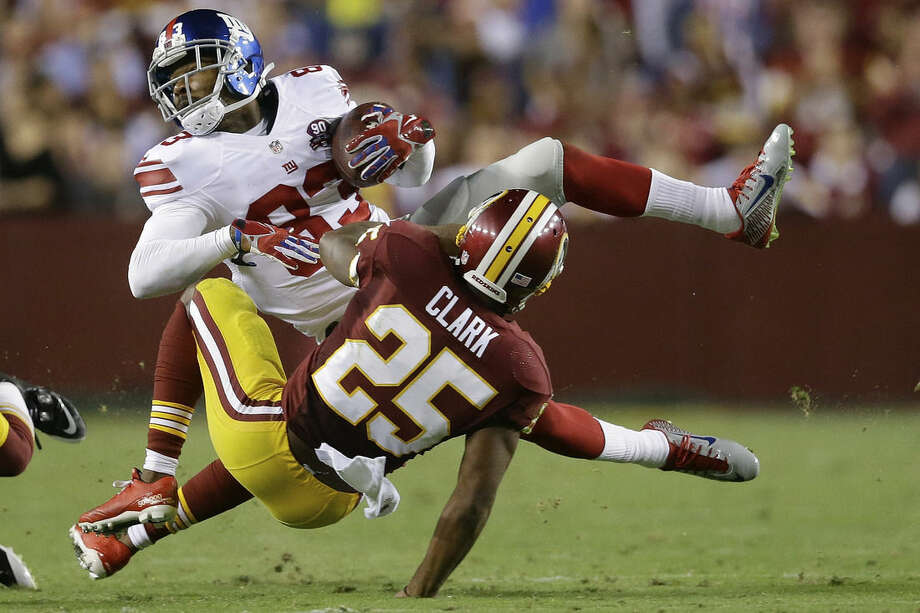 New York Giants wide receiver Preston Parker (83) is stopped by Washington Redskins free safety Ryan Clark (25) during the first half of an NFL football game in Landover, Md., Thursday, Sept. 25, 2014. (AP Photo/Patrick Semansky)