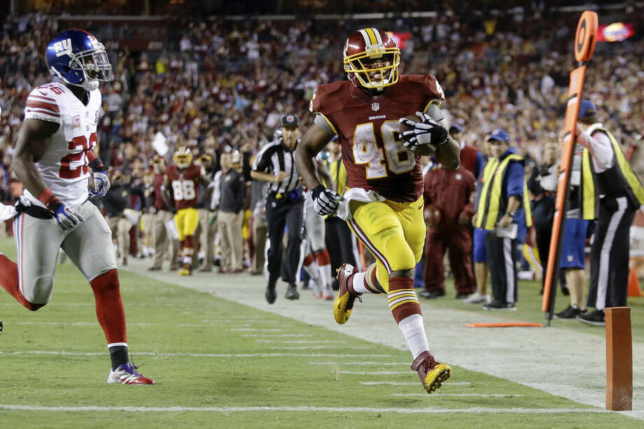 Washington Redskins running back Alfred Morris (46) steps into the end zone for a touchdown as New York Giants strong safety Antrel Rolle (26) pursues during the second half of an NFL football game in Landover, Md., Thursday, Sept. 25, 2014. (AP Photo/Patrick Semansky)