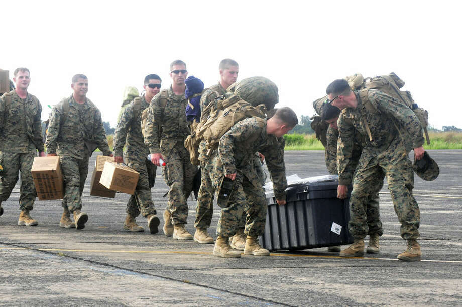 """U.S marines arrival at the Roberts International airport in Monrovia, Liberia, Thursday, Oct. 9, 2014. Six U.S. military planes arrived Thursday at the epicenter of the Ebola crisis, carrying more aid and American Marines into Liberia, the country hardest hit by the deadly disease that has devastated West Africa and stirred anxiety across a fearful world. At a World Bank meeting in Washington, the presidents of several West African countries struggling with Ebola pleaded for help, with one calling the epidemic """"a tragedy unforeseen in modern times."""" (AP Photo/Abbas Dulleh)"""