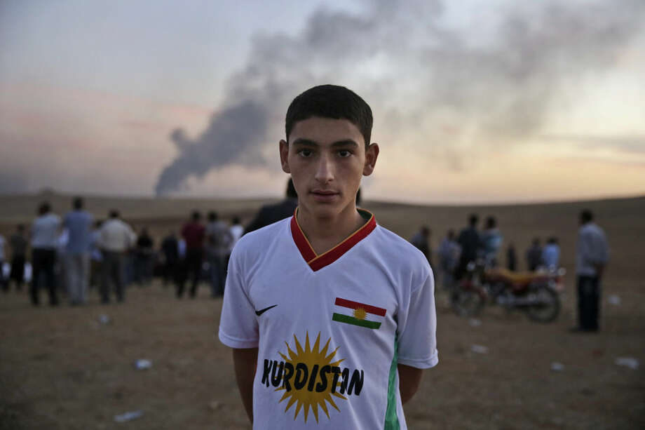 A Turkish Kurdish boy stands on a hilltop in the outskirts of Suruc, at the Turkey-Syria border, as he and others watch smoke from a fire caused by the US-led coalition aircrafts, in Kobani, Syria, Thursday, Oct. 9, 2014. Kobani, also known as Ayn Arab, and its surrounding areas, has been under assault by extremists of the Islamic State group since mid-September and is being defended by Kurdish fighters.(AP Photo/Lefteris Pitarakis)