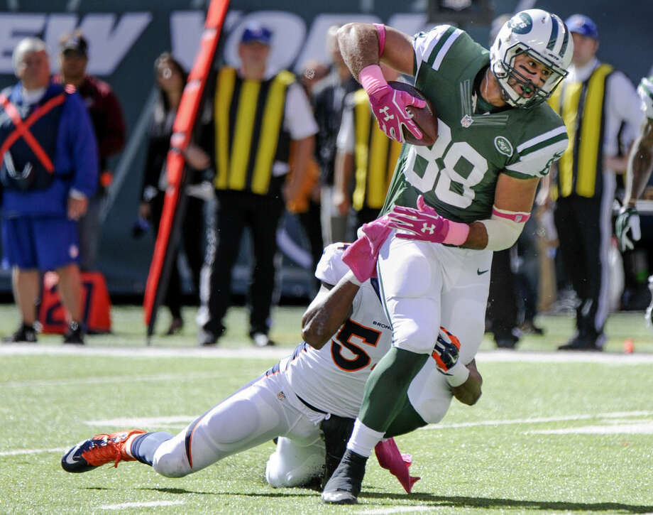 New York Jets tight end Jace Amaro (88) is tackled by Denver Broncos outside linebacker Brandon Marshall (54) in the first quarter of an NFL football game, Sunday, Oct. 12, 2014, in East Rutherford, N.J. (AP Photo/Bill Kostroun)