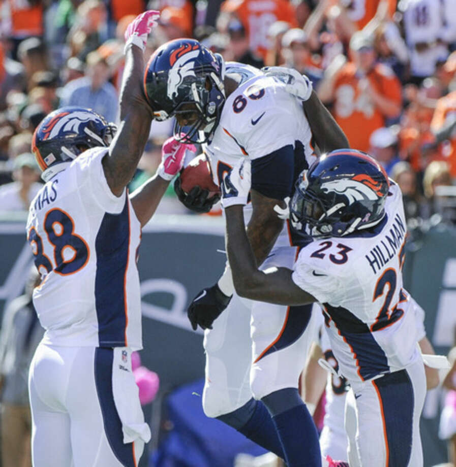 Denver Broncos tight end Julius Thomas (80) celebrates with wide receiver Demaryius Thomas (88) and running back Ronnie Hillman (23) after catching a pass for a touchdown against the New York Jets during the second quarter of an NFL football game, Sunday, Oct. 12, 2014, in East Rutherford, N.J. (AP Photo/Bill Kostroun)