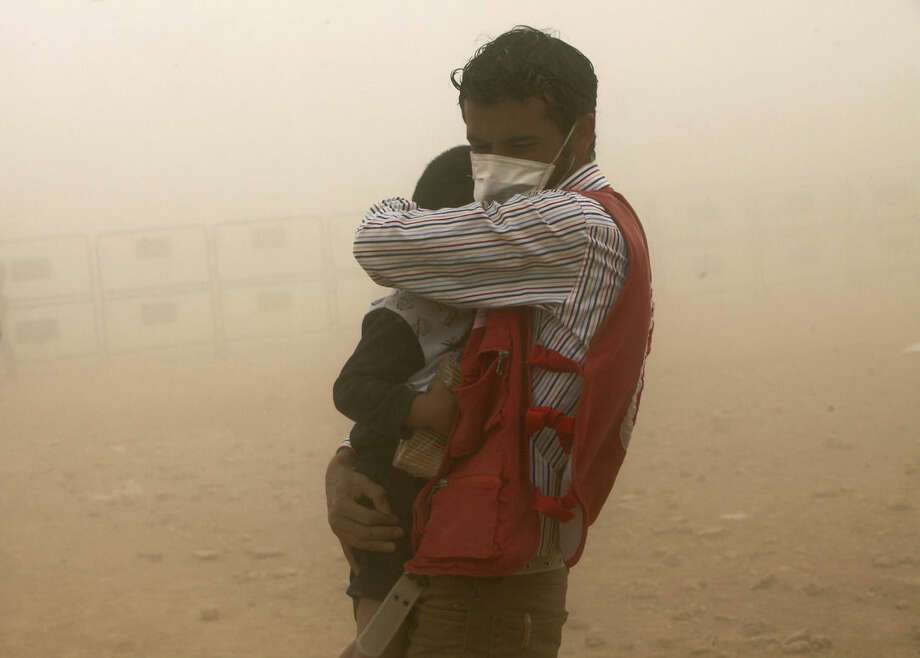 FILE - In this Wednesday, Sept. 24, 2014 file photo, a Turkish aid worker protects a Syrian refugee child during a sand storm at Yumurtalik crossing gate near Suruc, Turkey. The predominantly Kurdish town of Kobani has been transformed from a dusty backwater into a symbol of resistance for Kurds around the world. The battle against the Islamic State group is now playing out in Kobani's streets and alleyways - a fight being watched by scores of Syrian and Turkish Kurds, as well as dozens of journalists, through binoculars from hilltops and farms just across the border in Turkey. The international media spotlight, has helped turn the defense of Kobani into a very public test for the American-led international effort to roll back and ultimately destroy the Islamic State group. (AP Photo/Burhan Ozbilici, File)