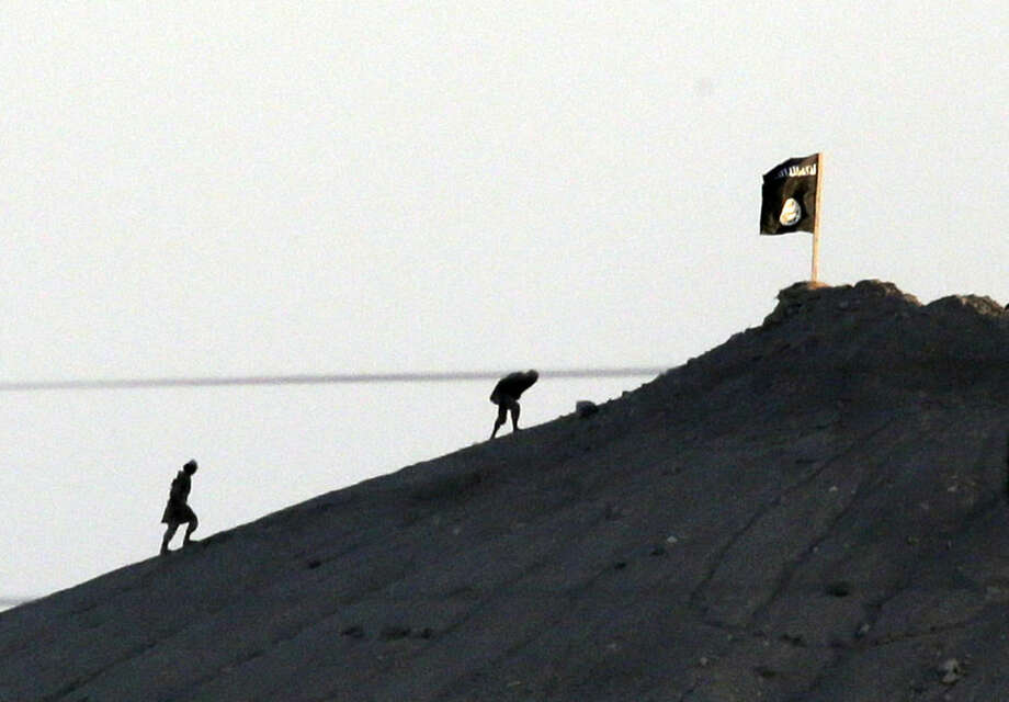 FILE In this Oct. 6, 2014 file photo, shot with an extreme telephoto lens and through haze from the outskirts of Suruc at the Turkey-Syria border, militants with the Islamic State group are seen after placing their group's flag on a hilltop at the eastern side of the town of Kobani, Syria. The predominantly Kurdish town of Kobani has been transformed from a dusty backwater into a symbol of resistance for Kurds around the world. The battle is now playing out in Kobani's streets and alleyways - a fight being watched by scores of Syrian and Turkish Kurds, as well as dozens of journalists, through binoculars from hilltops and farms just across the border in Turkey. The international media spotlight, has helped turn the defense of Kobani into a very public test for the American-led international effort to roll back and ultimately destroy the Islamic State group. (AP Photo/Lefteris Pitarakis)