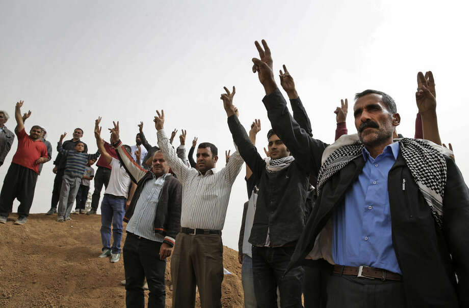 FILE - In this Saturday, Oct. 11, 2014 file photo, mourners flash the victory sign as they sing a nationalistic Kurdish song at a cemetery in Suruc, on the Turkey-Syria border, during the funeral of two Syrian Kurdish fighters, who were killed in the fighting with the militants of the Islamic State group in Kobani, Syria. The predominantly Kurdish town of Kobani has been transformed from a dusty backwater into a symbol of resistance for Kurds around the world. The battle is now playing out in Kobani's streets and alleyways - a fight being watched by scores of Syrian and Turkish Kurds, as well as dozens of journalists, through binoculars from hilltops and farms just across the border in Turkey. The international media spotlight, has helped turn the defense of Kobani into a very public test for the American-led international effort to roll back and ultimately destroy the Islamic State group. (AP Photo/Lefteris Pitarakis)