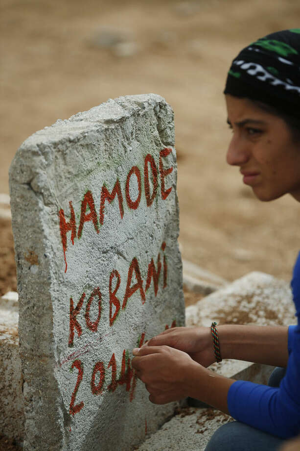 FILE - In this Saturday, Oct. 11, 2014 file photo, a relative sits by the grave of her loved one, going by the name of Hamode, a Kurdish fighter from Kobani, who was killed in the fighting with militants of the Islamic State group in Kobani, Syria, and was buried at a cemetery in Suruc, Turkey. The predominantly Kurdish town of Kobani has been transformed from a dusty backwater into a symbol of resistance for Kurds around the world. The battle is now playing out in Kobani's streets and alleyways - a fight being watched by scores of Syrian and Turkish Kurds, as well as dozens of journalists, through binoculars from hilltops and farms just across the border in Turkey. The international media spotlight, has helped turn the defense of Kobani into a very public test for the American-led international effort to roll back and ultimately destroy the Islamic State group. (AP Photo/Lefteris Pitarakis, File)
