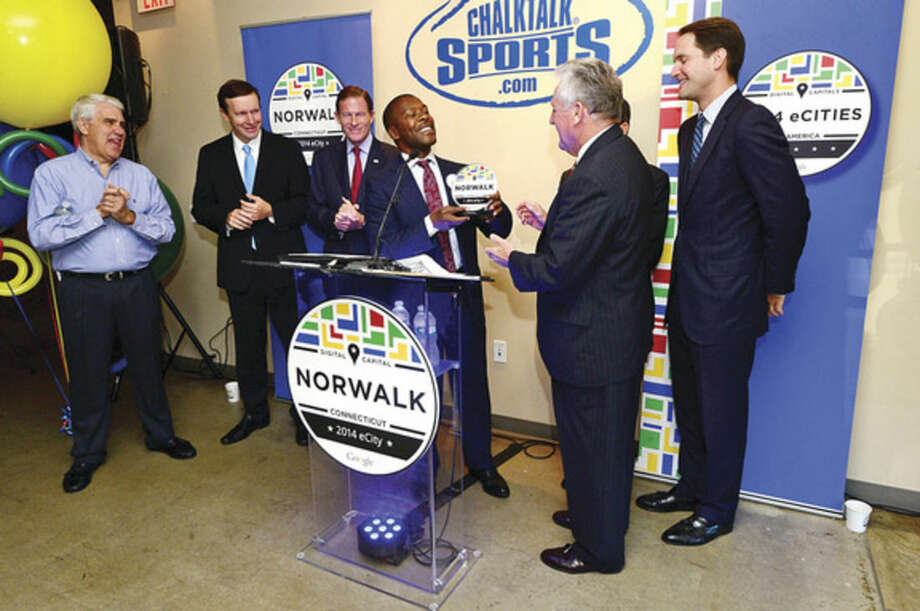 Hour photo / Erik Trautmann Google spokesperson William Floyd announces Norwalk as the 2014 eCity capital of Connecticut Wednesday as he presents the award to Norwalk mayor Harry Rilling at Chalktalk Sports on Woodward Ave. The eCity Awards recognize the strongest online business community in each state - the digital capitals of America. Google's award recognizes the city's innovative businesses by holding the community celebration with state and local elected officials, representatives of the Norwalk Chamber of Commerce and representatives from local small businesses.