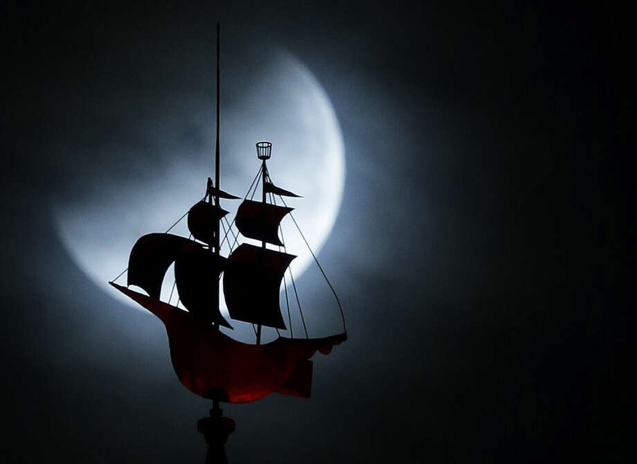 The Earth's shadow begins to fall on the moon during a total lunar eclipse, as it goes behind a weathervane shaped like a Spanish galleon on the Freedom Tower, Wednesday, Oct. 8, 2014 in Miami. (AP Photo/Wilfredo Lee)